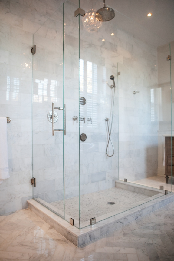 Crystal clear shower reflects crystal chandelier in luminous Master Bath.