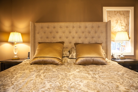 Golden satins and earthy velvets -- all custom for the project--adorn the bed.