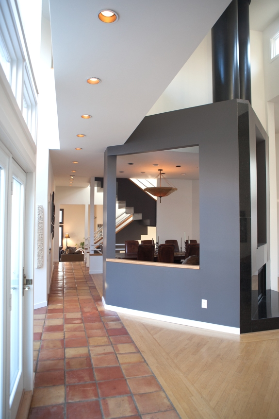 Fireplace and fireplace wall, highlighted in charcoal glossy paint, are  sculpture in the Entry Hall.